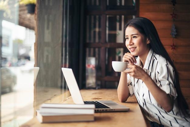 Schönheit, die mit laptop-computer am kaffeestubecafé arbeitet