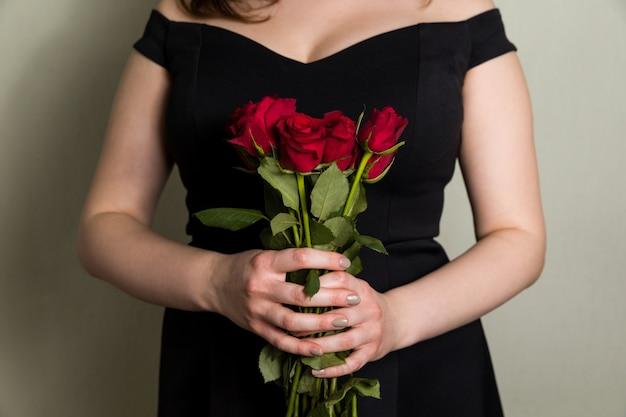 Schönheit, die rotrosenblumenstrauß, romantische valentinsgrußtagesüberraschung hält.