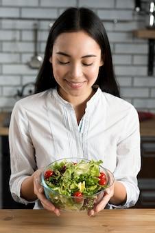 Schönheit, die salat in der schüssel hält