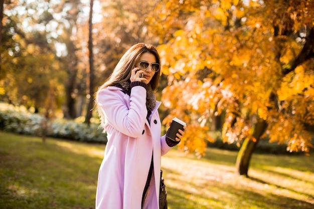 Schönheit, die telefon verwendet und kaffee im herbstpark trinkt