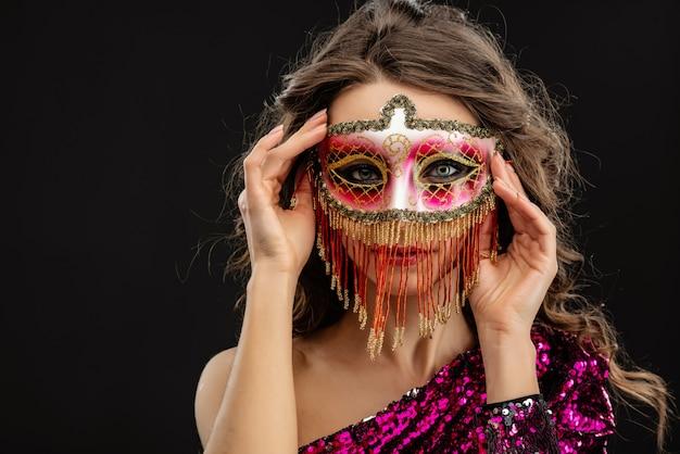 Schönheit, die venetianische karnevalsmaske gegen schwarzen hintergrund trägt