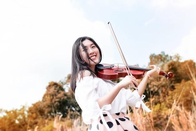 Schönheit, die violine mit lächeln und glücklichem gefühl spielt, genießen mit streichinstrument, in einem park, weinleseton, undeutliches licht herum