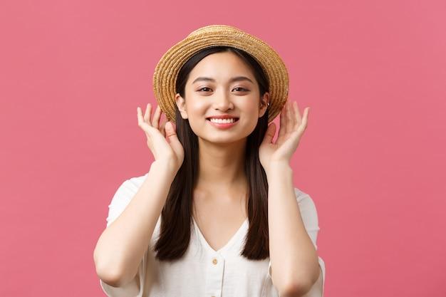 Schönheit, emotionen der menschen und freizeit- und urlaubskonzept. schöne asiatische frau, die im laden einkauft, einen neuen strohhut auswählt, erfreut lächelt und ein sommeroutfit über rosafarbenem hintergrund kauft