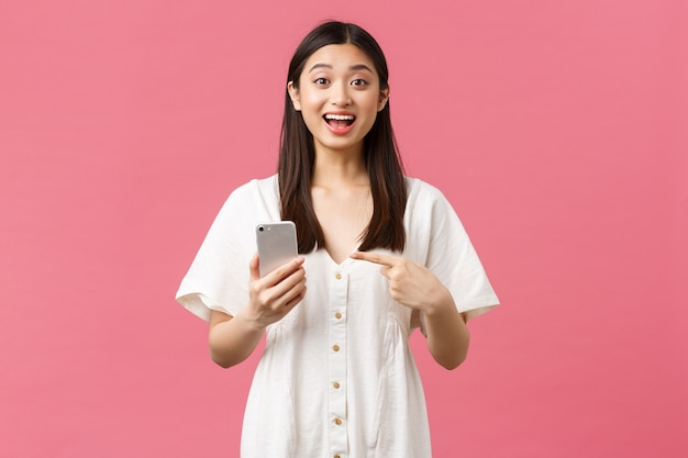Schönheit, emotionen der menschen und technologiekonzept. erfreut gut aussehendes asiatisches mädchen im weißen kleid, das mit dem finger auf das smartphone zeigt, als tolle anwendung gefunden, handy-app empfehlen