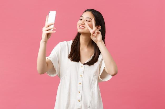 Schönheit, emotionen der menschen und technologiekonzept. feminine gut aussehende, stilvolle asiatische bloggerin, die selfie auf der smartphone-kamera macht, glücklich am handy lächelt und rosa hintergrund steht.
