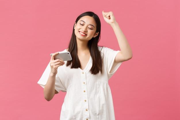 Schönheit, emotionen der menschen und technologiekonzept. mädchen genießen das ansehen von lieblings-k-pop-musikvideos auf dem smartphone, tanzen zu schlagen, schauen auf das handy und singen, rosa hintergrund.