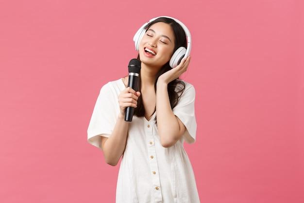 Schönheit, emotionen der menschen und technologiekonzept. sorglos glückliches asiatisches mädchen mit handy-karaoke-anwendung, gesang im mikrofon, musik in kopfhörern hören, rosa hintergrund.