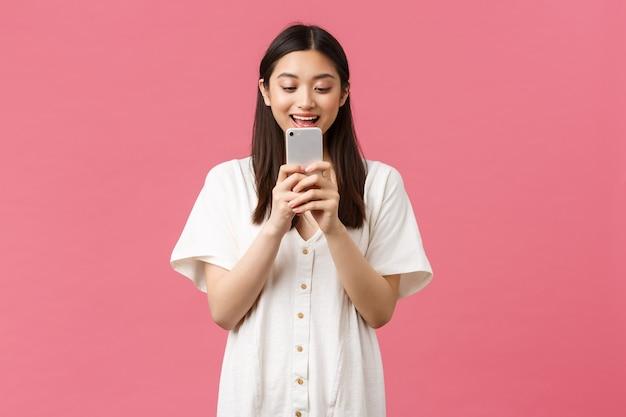 Schönheit, emotionen und technologiekonzept. aufgeregter asiatischer mädchenblogger, der das handy mit erstauntem glücklichem gesicht betrachtet, sms schreibt oder anwendung verwendet, videos auf smartphone ansieht, rosa hintergrund.
