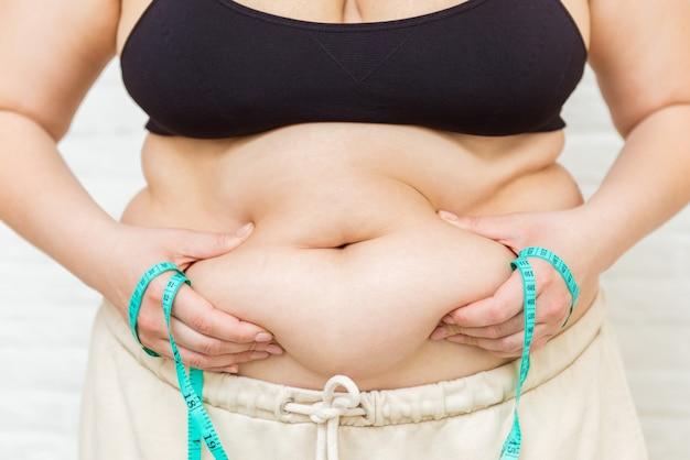 Schönheit, form, gesundheit und weibliches konzept des gesundheitswesens. fette junge frau, die ihren magen, übergewicht oder fettleibigkeit auf weißem hintergrund misst. depressives übergewichtiges mädchen mit maßband