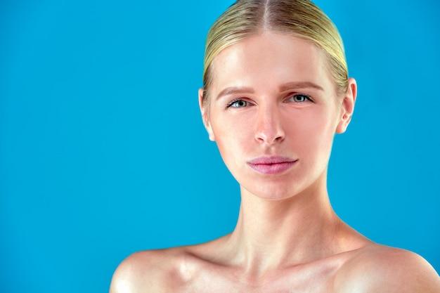 Schönheit frau gesicht porträt. schönes spa-modell mädchen mit perfekter frischer sauberer haut. blonde frau, die kamera betrachtet und lächelt. jugend- und hautpflegekonzept. blauer hintergrund grau