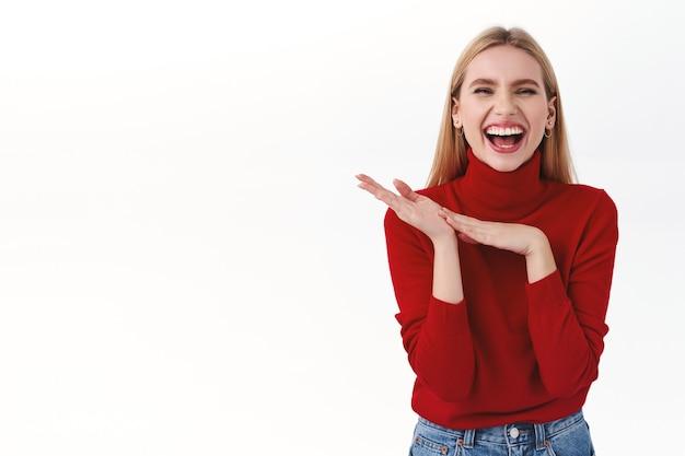 Schönheit, frauen und modekonzept. gut aussehende erfolgreiche blonde geschäftsfrau im roten rollkragenpullover, hände reiben, wie man es sich wünscht