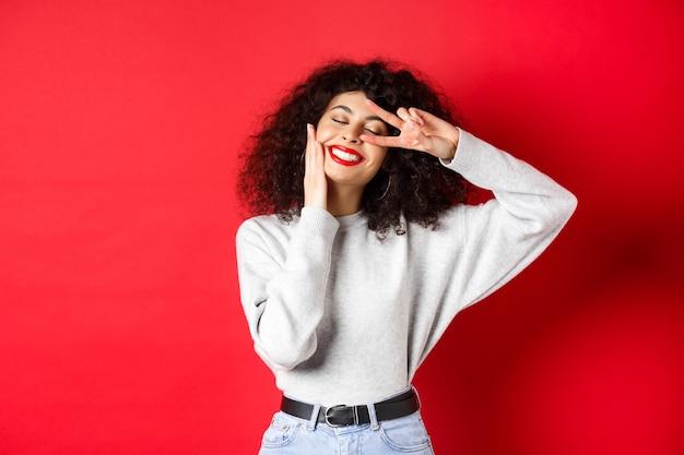 Schönheit. hübsche dame mit lockigem haar und roten lippen, gesicht mit make-up berührend und v-zeichen auf auge zeigend, sorglos lächelnd, gegen studiohintergrund stehend.