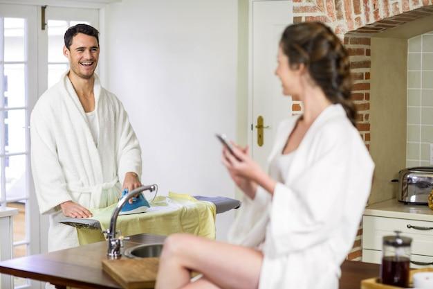 Schönheit im bademantel, der auf küchenarbeitsplatte sitzt und eine textnachricht auf smartphone während bügelnde kleidung des mannes hinter ihr schreibt