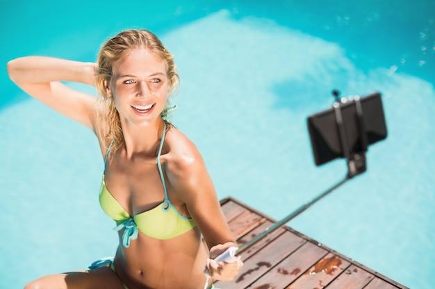 Schönheit im bikini, der ein selfie durch poolseite nimmt