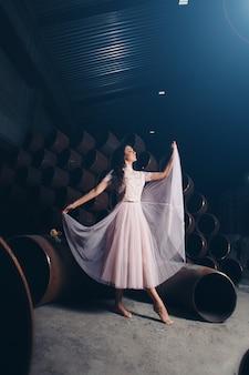 Schönheit im hellrosa kleid, das barfuß auf den hintergrund von großen eisenrohren tanzt