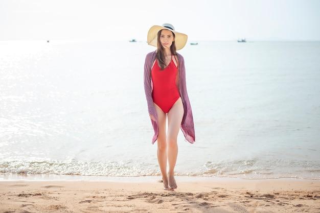 Schönheit im roten badeanzug geht vom meer, sommer-konzept
