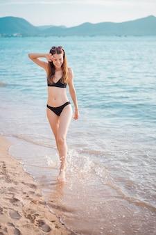 Schönheit im schwarzen bikini geht vom meer, sommerkonzept