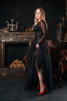 Schönheit im schwarzen kleid mit korsett steht in den roten schuhen