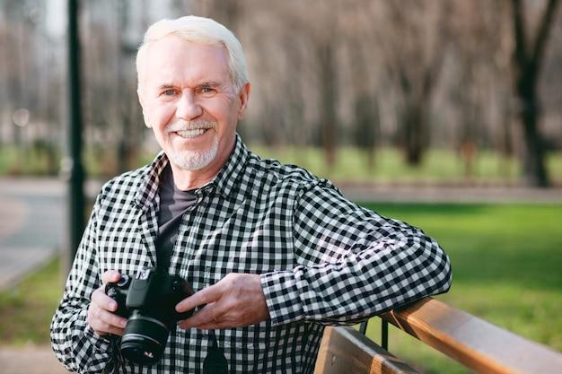 Schönheit in bildern. energetischer reifer mann, der kamera benutzt und zur kamera grinst