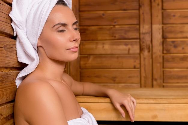 Schönheit in der sauna. attraktive junge frau in handtuch eingewickelt, die sich in der sauna entspannt und die augen geschlossen hält