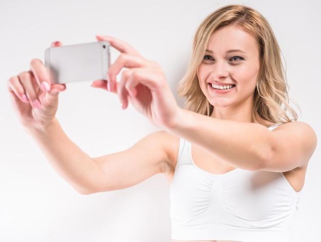 Schönheit in der weißen baumwollunterwäsche, die selfie nimmt.