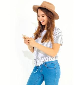 Schönheit in der zufälligen hippiesommerkleidung ohne make-up in hörender musik des braunen hutes im telefon mit den kopfhörern lokalisiert auf weiß