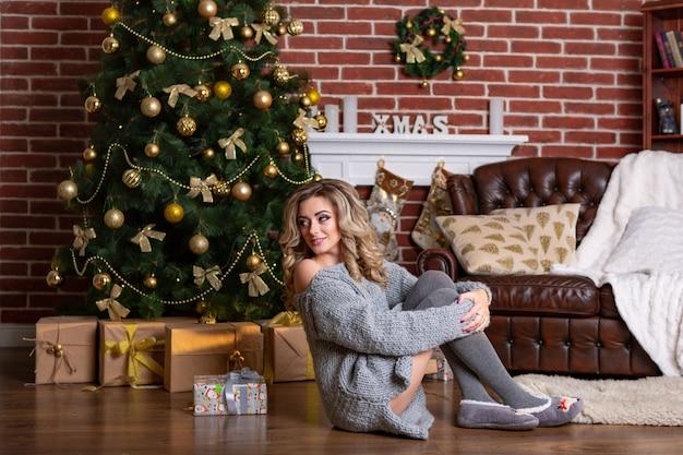 Schönheit in einem gestrickten grauen kleid sitzt auf dem boden nahe dem weihnachtsbaum und einem lehnsessel mit geschenken im wohnzimmer