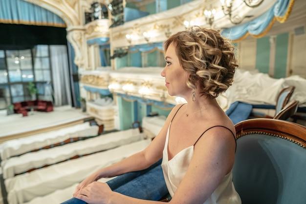 Schönheit in einem kleid allein auf dem balkon eines klassischen leeren theaters betrachtet das stadium und den innenraum