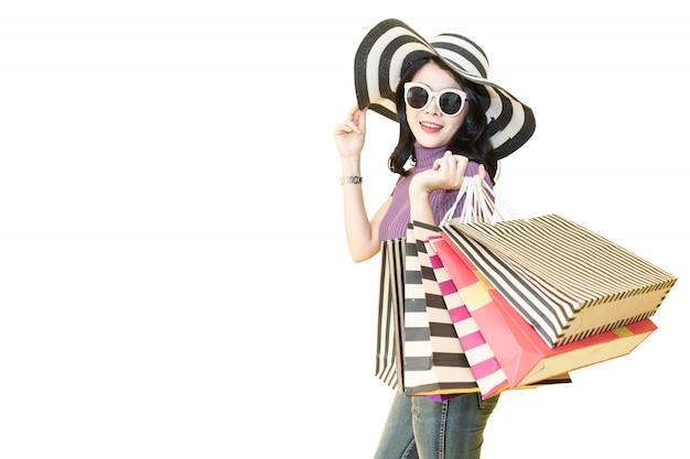 Schönheit kauft im mall. tragende gläser und hut der frau, die einkaufstaschemode im kaufhaus halten.