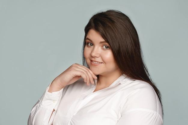 Schönheit, körperpositivität, stil, mode und weiblichkeit. übergewichtige junge frau in übergröße mit perfekter haut, ordentlichem haar und fröhlichem lächeln, das posiert, ihr kinn berührt und ein weißes hemd trägt