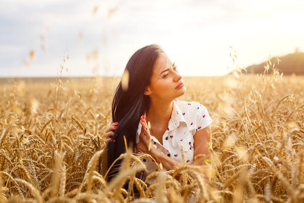 Schönheit mädchen im freien genießen natur auf weizenfeld schönes modell mädchen mit langen haaren auf goldenen fi...