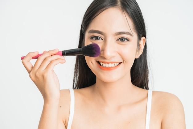 Schönheit make-up asiatische frau lächelnde nahaufnahme. schöne junge frau, die grundierungspulver anwendet oder mit make-uppinsel errötet. asiatisches kaukasisches modell der gemischten rasse.