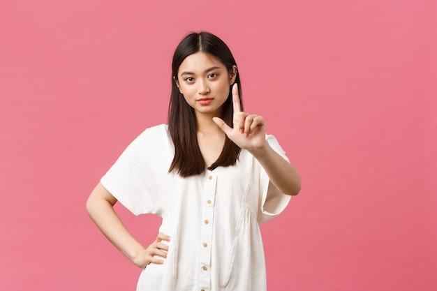 Schönheit, menschengefühle und sommerfreizeit- und urlaubskonzept. freches und selbstbewusstes, stilvolles asiatisches mädchen erklärt die regel, zeigt nicht so schnelle gesten, schüttelt den finger als schelte oder beschränkt jemanden.
