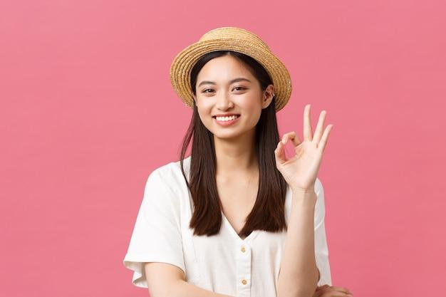 Schönheit, menschengefühle und sommerfreizeit- und urlaubskonzept. fröhliches süßes asiatisches mädchen im strohhut, das ein okayzeichen zeigt und glücklich lächelt, produkt oder geschäft empfehlen, ratschläge geben, tollen ort genehmigen.