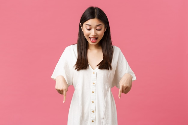 Schönheit, menschengefühle und sommerfreizeit- und urlaubskonzept. überraschtes und aufgeregtes kawaii asiatisches mädchen im weißen kleid, das mit amüsiertem glücklichem gesicht, rosa hintergrund zeigt und nach unten schaut