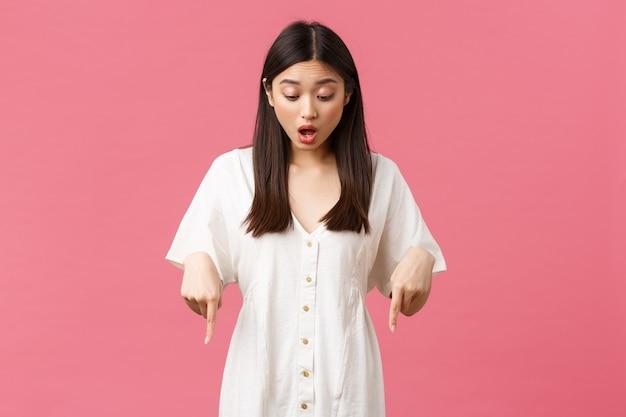 Schönheit, menschengefühle und sommerfreizeit- und urlaubskonzept. überraschtes und aufgeregtes kawaii asiatisches mädchen im weißen kleid, das mit amüsiertem glücklichem gesicht, rosafarbenem hintergrund zeigt und nach unten schaut.