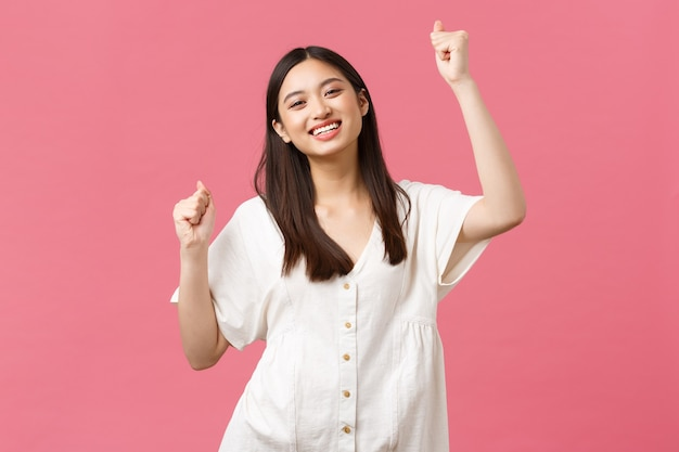 Schönheit, menschengefühle und sommerfreizeitkonzept. fröhliches, charismatisches asiatisches mädchen, das singt, glück und freude fühlt, auf party feiert, lebhaft mit erhobenen händen tanzt, lächelt