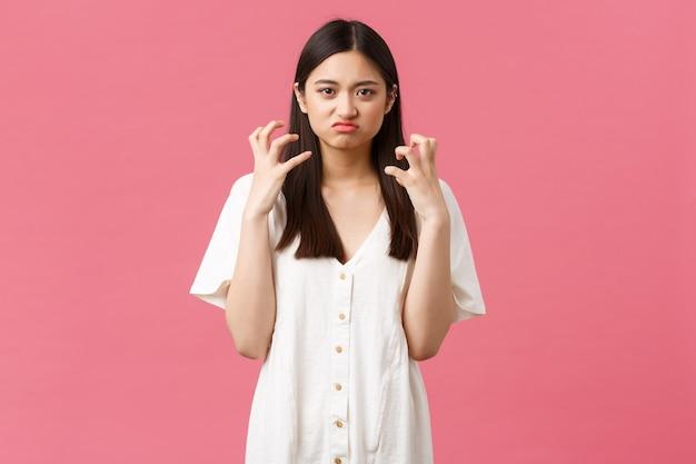 Schönheit, menschengefühle und sommerfreizeitkonzept. verrückte und angespannte junge asiatin verliert die kontrolle über emotionen, drückt die hände wütend und verzieht das gesicht, hasst jemanden, rosa hintergrund.