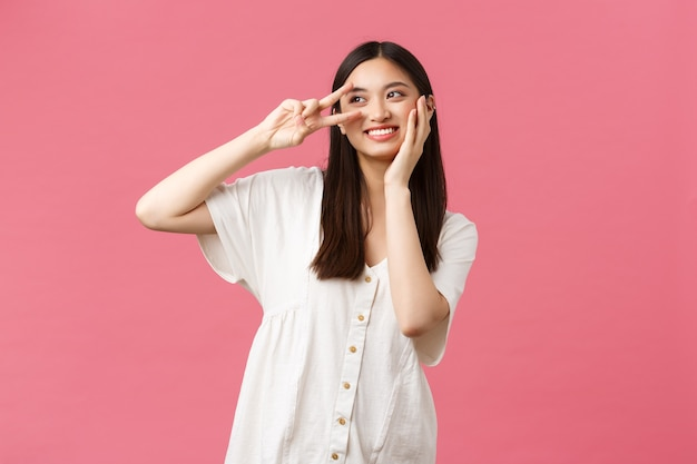 Schönheit, menschengefühle und sommerfreizeitkonzept. verträumtes und romantisches süßes lächelndes asiatisches mädchen, das nachdenklich wegschaut, während es weiche haut im gesicht berührt und friedenszeichen, rosa hintergrund zeigt