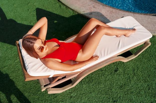 Schönheit mit dem perfekten körper, der auf sunbed ein sonnenbad nimmt