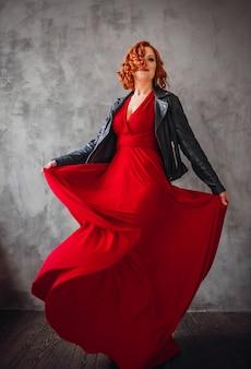 Schönheit mit dem roten haar und im roten kleid mit lederjacke wirft vor einer grauen wand auf