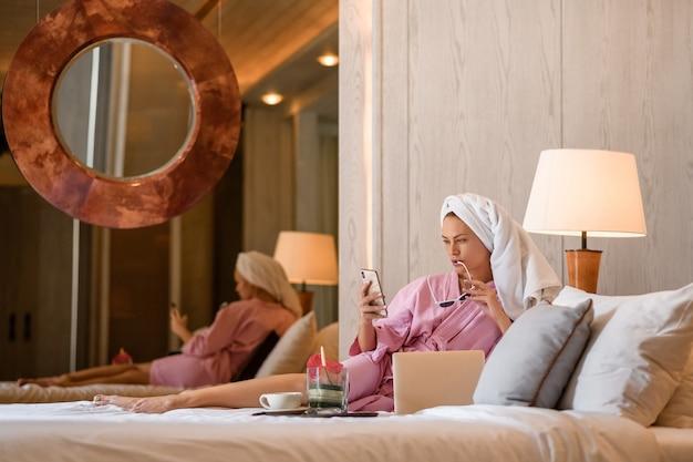 Schönheit mit tuch auf kopf zu hause sprechend am telefon im schlafzimmer. morgenroutine.