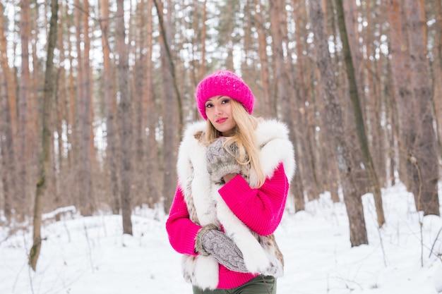 Schönheit, mode, menschenkonzept - attraktive blonde frau, die im winter in rosa hut und pullover geht