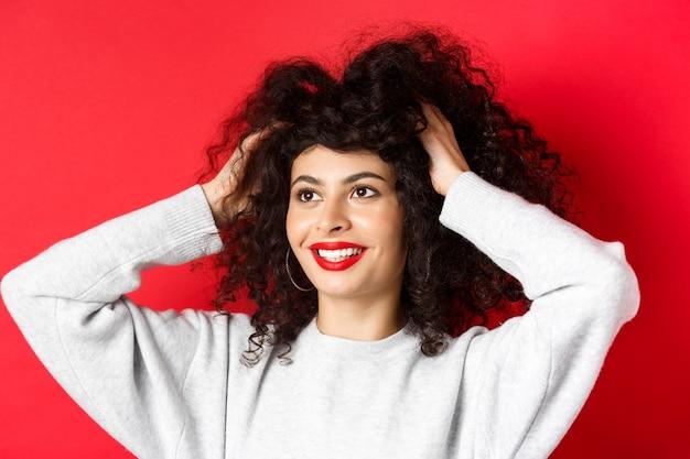 Schönheit. nahaufnahmeporträt der sorglosen frau, die ihr lockiges haar berührt und glücklich beiseite auf logo schaut, lächelnd mit weißen zähnen und roten lippen, studiohintergrund.