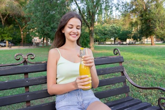 Schönheit öffnet eine flasche frischen kalten saft auf der bank im park am heißen sommertag