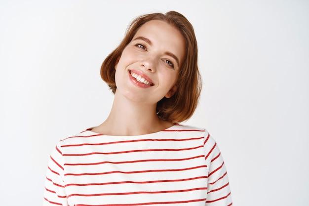 Schönheit. porträt eines fröhlichen mädchens mit kurzer frisur, geneigtem kopf und freundlichem lächeln, glücklich aussehend, gegen weiße wand stehend