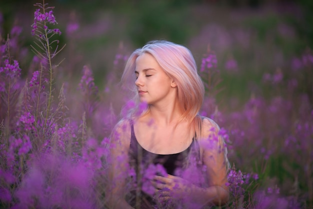 Schönheit romantisches mädchen im freien. schönes jugendmodell mit rosa haarmädchen auf dem feld von weidenröschen im sonnenaufgang.