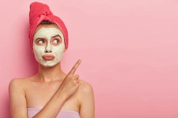Schönheit, spa, behandlungskonzept. unglückliche unzufriedene frau spitzt lippen, trägt tonmaske zur verjüngung auf, in badetuch gewickelt, zeigt auf kopierfläche gegen rosa wand, will schnelles ergebnis