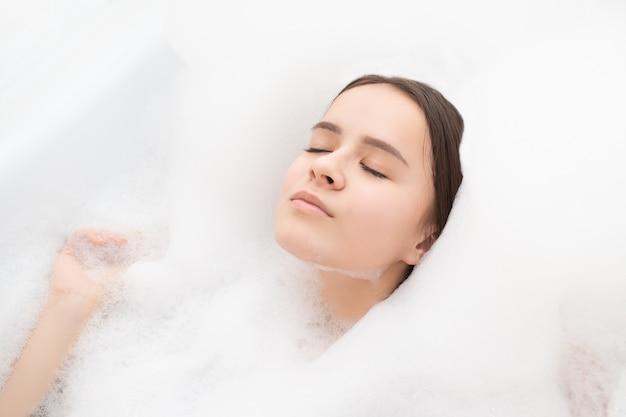 Schönheit, spa, körperpflege. junge frau entspannt sich im bad mit schaum