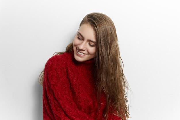 Schönheit, stil, mode, kleidung und jahreszeiten konzept. bild der entzückenden niedlichen jungen dame mit breitem, charmantem lächeln, das isoliert posiert und warmen kuscheligen strickpullover trägt, der von ihrer mutter gemacht wird
